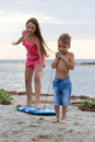Kids playing with surfing board on beach happy little children the Stock Photos