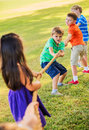 Kids playing tug of war on grass group Royalty Free Stock Image