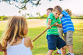 Kids playing tug of war group happy young children outside on grass Stock Photos