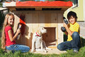 Kids preparing a shelter for their new puppy dog finishing and painting the doghouse Stock Image