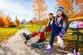 Kids putting on roller blades and years old couple of school boy an girl in warm autumn clothes Stock Image