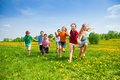 Kids racing large group of running in the dandelion spring field Stock Photo