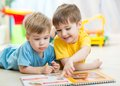 Kids read a book at home or nursery brothers Stock Photo