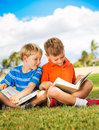 Kids reading books happy young boys outside friendship and learning concept Stock Photography