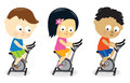 Kids riding exercise bikes children of different nationalities stationary bicycles Royalty Free Stock Image