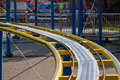 Kids roller coaster yellow rails in amusement park. Royalty Free Stock Photo