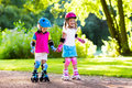 Kids roller skating in summer park Royalty Free Stock Photo