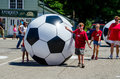 Kids rolling giant soccer balls team and mom roll down the street during the peach festival parade in coloma michigan Royalty Free Stock Image