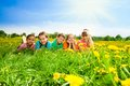 Kids in a row in flower field group of happy diversity looking boys and girls laying dandelion fields Stock Image