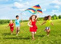 Kids run with kite group of four running in the park happy and smiling on summer sunny day Stock Photo