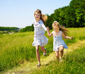 Kids running across green grass outdoor. Royalty Free Stock Images