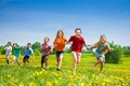 Kids running in the field group of seven happy park boys and girls black and caucasian Stock Photo