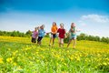 Kids running group of happy in the yellow flowers field summer day Royalty Free Stock Images