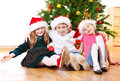 Kids in Santa hats embracing Stock Photos