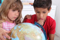 Kids sat with globe boy and girl Stock Photo