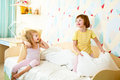 Kids sisters play on bed playing the indoors Royalty Free Stock Image
