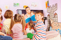 Kids sit around teacher and listening to story Royalty Free Stock Photo