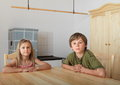 Kids sitting behind wooden table two boy and girl a in front of wardrobe and historical furnace Stock Image