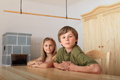 Kids sitting behind wooden table two boy and girl a in front of wardrobe and historical furnace Royalty Free Stock Photo