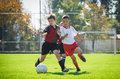 Kids soccer boys kicking football on the sports field Royalty Free Stock Photos