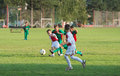 Kids soccer dribbling on football match in field Stock Photos
