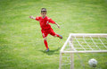 Kids soccer little boy shooting at goal Stock Photo