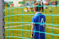 Kids soccer match. Young boy as a soccer goalkeeper during football match ready to save Royalty Free Stock Photo
