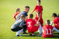 Kids soccer waiting in out with coach Royalty Free Stock Photo