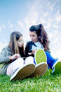Kids on social networks two young girls having fun with a tablet and a smartphone Royalty Free Stock Photo