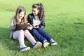 Kids on social networks two young girls in the park having fun with wireless gadgets Royalty Free Stock Photo