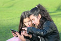 Kids on social networks two young girls in the park having fun with wireless gadgets Royalty Free Stock Photos