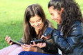 Kids on social networks two young girls in the park having fun with wireless gadgets Stock Image