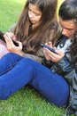 Kids on social networks two young girls in the park having fun with wireless gadgets Stock Images