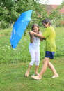 Kids splashed with garden hose barefoot boy and girl in wet clothes and using blue umbrella as a shield Stock Photo