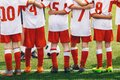 Kids sports team putting hands on top of each other as symbol of successful collaboration