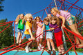 Kids standing in a row on red ropes of playground large group net summer Stock Images
