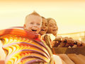 Kids on a summertime roller coaster ride three excited warm summer evening shot at sunset at an amusement park Stock Photos