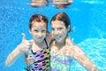 Kids swim in pool underwater girls swimming playing and having fun children water sport Stock Photo