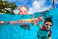 Kids in swimming pool above and underwater photo of Stock Images