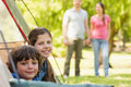 Kids in tent with couple in background at park Royalty Free Stock Photos