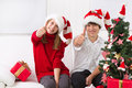 Kids thumbs up on christmas cheerful under the tree with thumb Royalty Free Stock Photos