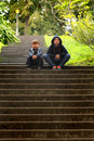 Kids tired of waiting two cute little boys sitting on some big concrete steps bored and shallow depth field copy space Royalty Free Stock Photos