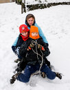 Kids tobogganing in the snow Royalty Free Stock Image
