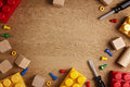 Kids toys background. Colorful toy tools, construction blocks and cubeson wooden table. Top view. Flat lay. Copy space Royalty Free Stock Photo
