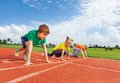 Kids in uniforms on bended knee ready to run Royalty Free Stock Photo