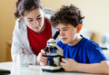 Kids using microscope examining preparation under the Royalty Free Stock Photography