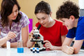 Kids using microscope examining preparation under the Stock Photography