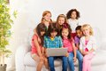 Kids watch movie from laptop large group of sitting occupied on the couch with looking at screen and smiling Royalty Free Stock Photo