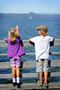 Kids watching a sailboat Royalty Free Stock Image