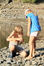Kids watching a shell by a lake standing little barefoot girl in blue t shirt with cherries and cap boy in grey shorts and crocks Stock Image